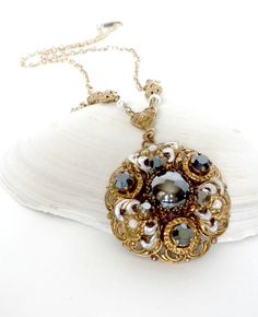 This is a vintage 50s Gothic Victorian style gold tone filigree pendant chain necklace with black rhinestones, white faux pearls and a round hematite glass cabochon in the center. It has silver enamel swirl accents. Not stamped but is likely West German. Measurements: Necklace - 24 inches. Pendant, including heart shaped junction - 2.5 inch drop. The pendant alone is 1.75 inches.  Condition: Great! The metal does have a small amount of wear and patina. All stones are secure and show little…