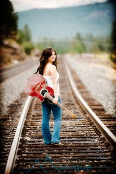 I love her hair, her outfit, the railroad, and the guitar!