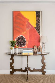 This transitional console design is achieved through a mix of contemporary art and an antique console table. Design by Woody Argall Design.
