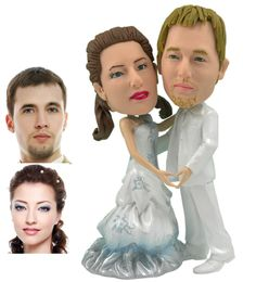 Made to Look like you. This personalized wedding cake topper shows a couple facing each other and making a heart shape with each others hands. The groom is dressed in white from head to toe and the bride wears a pearlescent light blue dress with flower ornaments through out.