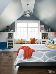To make the most of the attic's sloped ceilings, homeowners installed built-ins that offer plenty of storage and display space. A window seat showcases the room's abundant natural light, and a modern pendant light draws the eyes upward. A navy color palette, punctuated with pops of orange and yellow, creates a soothing bedroom atmosphere./