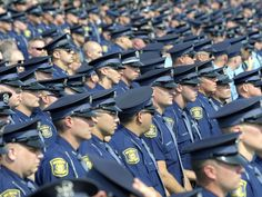 Michigan State Police troopers stand at ease before