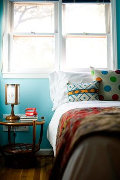 I wanted our guest bedroom to feel truly like a vacation, hence the bright Bahamian colors. It's a funny small nook upstairs that reminded me of a nautical space, so I ran with it. We have a few paintings of water and ships in here as well – maybe a little theme-y and literal, but I haven't wanted to repaint yet – ask my husband, this happens often, so I think it'll last. The wall is Benjamin Moore's Sea Isle.
