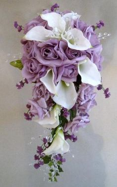 """Bridal cascading Bouquet is design with approx 9 white / cream latex calla lilies,10 large lavender roses,6 medium lavender roses, purple babies breath & approx 24 stems clear gemstones. (optional )     Hand wrapped with lavender & purple satin ribbon.    It measures approx 12"""" across and 23"""" long. by lakeisha"""