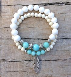 feather bracelet , beach bohemian bracelet , beach boho bracelet , beachcomber beach bracelet white / cream howlite beads 6mm with mint jade beads, silver tibetan style beads and a silver tone feather, threaded onto good quality jewellery elastic. wear it alone or stacked with other