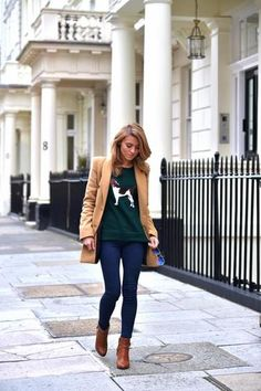 trending: the camel coat - styled with preppy hunter green graphic sweatshirt with canine applique, skinny jeans, + brown leather ankle boots