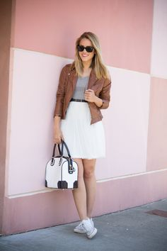 Gray shirt, brown leather jacket, white skirt with black belt, and white Converse.
