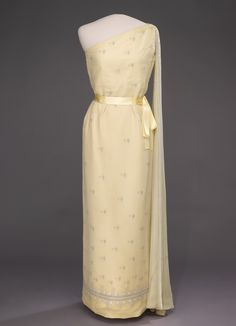 Jacqueline Kennedy wore this yellow silk evening gown with an overlay of crepe chiffon in 1961 for the Kennedy administration's first state dinner, for Tunisian president Habib Bourguiba. Oleg Cassini designed the gown.