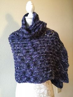 """It's that time of year where a sweater is just too warm, but a shirt alone leaves me chilled. And that is exactly why the Black Forest Wrap was created. I needed a comfy, cozy wrap that would look good and keep my shoulders warm. This wrap is double knit on Authentic Knitting Board's 28"""" knitting board. The sample used 745 yards of Red Heart Artesano yarn in Moonstruck, but unfortunately this yarn has been discontinued. I honestly think any medium worsted weight yarn that has a soft touch…"""