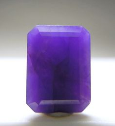 "A bright purple emerald cut Gel Sugilite. The name ""Gel"" is given to the translucent material that has good   crystallization and gives the finished gem a glassy look. It is rare and very prized. Less than 1% of the mined Sugilite is ""gel"".   This piece weighs 1.10 carat is well cut with good polish and has lighter purple color veins. From Hotazel.  From Mineral Auctions    via Sabrina Jordan"
