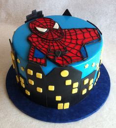 Spiderman Birthday Cake. 3 layer yellow cake with chocolate mousse, chocolate buttercream, fondant enrobing, skyline and Spidey.