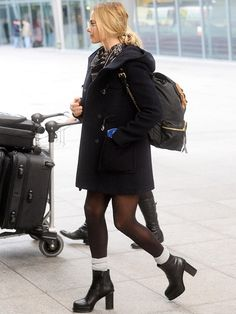 Margot Robbie wears a mini dress, peacoat, scarf, tights, gray socks, platform boots, and a Burberry backpack