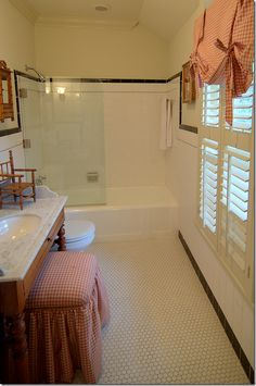 long and narrow simple bath - marble top vanity w sink + bench covered same as valence for putting on makeup, etc, Secondary bath for girl: partial glass door for tub/shower, small hexagonal tiles on floor, larger white tiles on walls.
