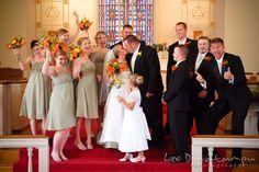 Best man, groomsmen, maid of honor, bridesmaids, and flower girl cheering at the kissing bride and groom. Best man and groomsman trying to lift up groom. Kent Island Methodist Church KIUMC Wedding Photographer Maryland