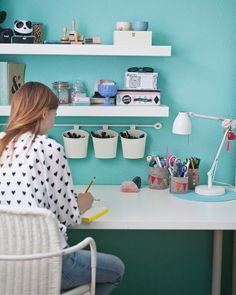 It can be tricky to keep a well-stocked desk space clear and tidy. Luzie's solution is to make the most of her wall; she keeps less essential stationery on her floating shelves, her favourite pens hanging from a rail, art pencils in drawers, and everything else in customised pen pots pushed to the side.
