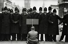 Don McCullin - Un manifestant anti-guerre solitaire affronte la police à Whitehall pendant la crise des missiles cubains, Londres, 1962.