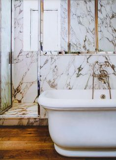 loving the mixed marble, oak flooring + curved free standing tub
