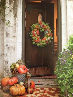 Fall - Autumn Decorating. Wood Front Door with Natural Elements Wreath, and Pumpkins.