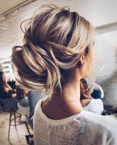 Messy neck-height low bun with whispy pieces-- the perfect updo for a wedding or special occasion.