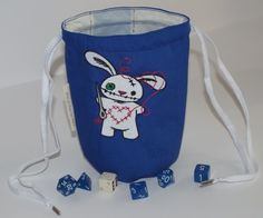 """This blue pouch has a machine embroidered white creepy bunny on it. Won't you be his friend? The outer fabric is blue with a blue & white lining fabric. This pouch is 6 1/2"""" high, 4"""" round. It will stand open on the game table. It has white shoe lace drawstrings on 2 sides. Embroidery pattern is ..."""
