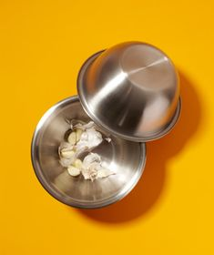Use two bowls to remove the peels from garlic cloves.