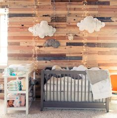 Honest Company - Whimsical boy's nursery features cloud pillows on wood plank wall over gray nursery crib filled with white and gray crib bedding next to white changing table.