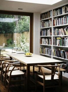 I was sitting in my dining room the other day when it struck me just how boring the room is. It's furnished with a table. And chairs. And that's it. What if — I began to wonder — one was surrounded by shelves and shelves of books in the dining room? Here are some inspiring examples.