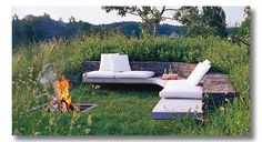 Fire pit in the ground with a built in bench; a modern feel, and blends right into a grassy meadow. Nice addition of cushions/pillows for comfy seating.