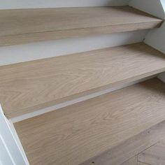 Massief eiken trapbekleding met traptreden in massief hout. De traptreden zijn rondom bekleed met eiken hout in 1bis selectie. Afgewerkt in skylt invisible look lak. De stootborden zijn wit gelaten voor het contrast.
