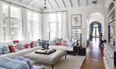 White walls, sheer withe drapes, and exposed white rafters combined with creamy upholstery, fishy prints, and tons coral and blue pillows make a perfect Florida family room in the chi chi polo community of Windsor, FL.