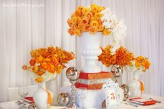 Pops of vibrant orange roses, orchids and ranunculus contrast beautifully with the milk white vases and table linens. Styling by Aileen Tran and Photography by Pam Scott Photography