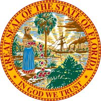 "Great Seal of the State of Florida. The seal features a shoreline on which a Seminole woman is spreading hibiscus flowers. Two of Florida's state tree, the Sabal palm, are growing. In the background a steamboat sails before a sun breaking the horizon, with rays of sunlight extending into the sky. The seal is encircled with the words ""Great Seal of the State of Florida"", and ""In God we Trust."""
