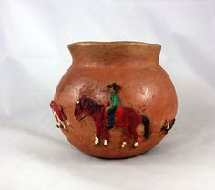 The round up is on! The cowboy herds the red cows with the aid of the cattle dog, nicely laid out around the body of the pottery jar.