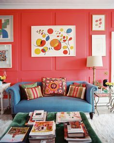 Cath Kidston Photo - A blue couch paired with red walls decorated with art