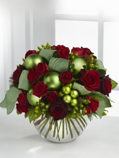 A Christmas Centerpiece with red flowers and green decorations in a bubble bowl