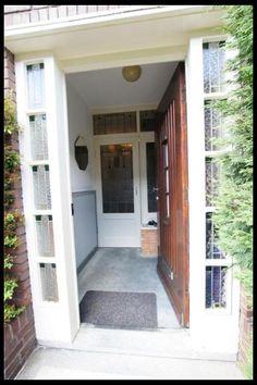 Voordeur met glas in lood, hal met granito vloer en klapdeuren uit een jaren dertiger woning in Haarlem