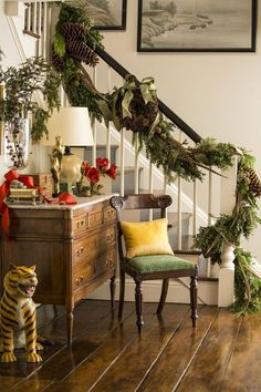A garland winding up the stair rail is decked with fresh-cut greens, holly branches, giant pinecones, and pheasant feathers..