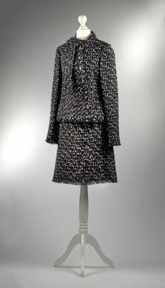 Chanel Auktion Lot 20: Chanel Kostüm aus der Autumn Collection 2006, schwarzer Boucléstoff mit weißen, grünen und rosafarbenen Einsprenkelungen, französische Größe 40 (entspricht deutscher Größe 38), Länge Blazer 57 cm, Ärmellänge außen 64, Rocklänge 54 cm, einfache Bundweite 36 cm. Mehr Information auf der Website