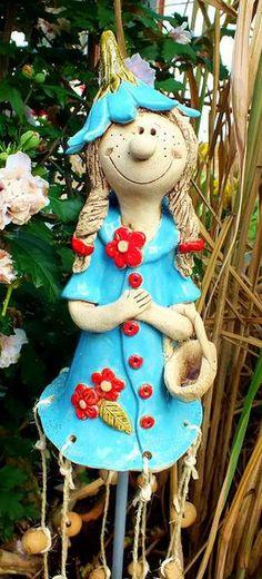 Eine hübsche Elfe als Windspiel für Ihren Garten. Die Figur wurde liebevoll teilglasiert und ist frostfest gebrannt. Am Saum ihres orangefarbenen Kleides sind 8 Stränge mit Keramikkugeln und...