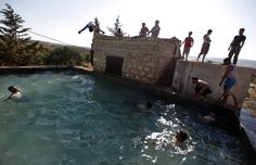 Free Syrian Army fighters swim in a pool on the outskirts of Aleppo, Syria on Tuesday, June 12, 2012. (AP Photo)
