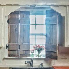 | kitchen | shutters | farmhouse style | vintage inspired | wood | diy | cottage kitchen | kitchen window | faucet | natural sun light |flowers in Mason jar