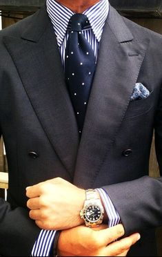 Navy double-breasted jacket, white shirt with navy dress stripes, navy tie with white pin dots.