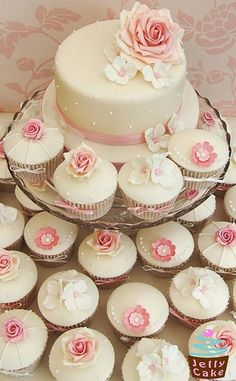 a beautiful cake surrounded by cupcakes with pink flowers
