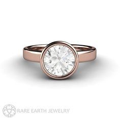 A classic solitaire engagement ring updated in a stylish contemporary bezel set design. At the center is a 6.5mm Forever Brilliant Moissanite,