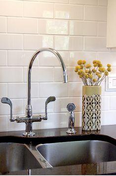 Kitchen clean and neutral with white 3x6 subway tile backsplash in kitchen behind black granite countertop