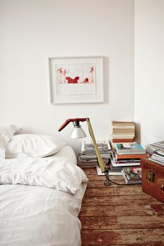 Airy bed on wood floor with book stacks.
