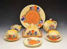Clarice Cliff (British, 1899-1972)' Crocus' pattern tea set comprising teapot, milk jug, butter dish and cover, two cups and saucers, dinner plate, side plate and egg cruet stand manufacturer's back stamps the teapot 13.5cm high, 16.5cm across (8)