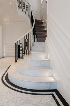 North London Townhouse - Stunning sweeping staircase with cast iron spindles. Marble inlay detail creates understated grandeur