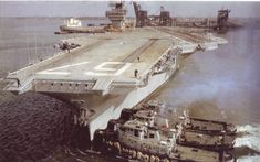 USS John F. Kennedy being pushed into position by the large harbor tugs in 1968, when JFK returned to her builder's yards for post-shakedown availability.