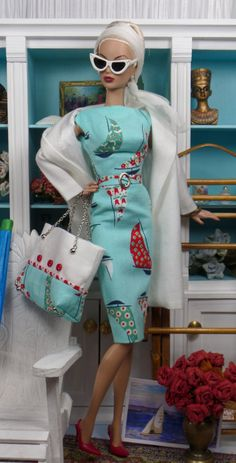 A nautical inspired ensemble features a boat neck sheath in fine printed cotton, fully lined in china silk, with attached belt, buckle and zipper